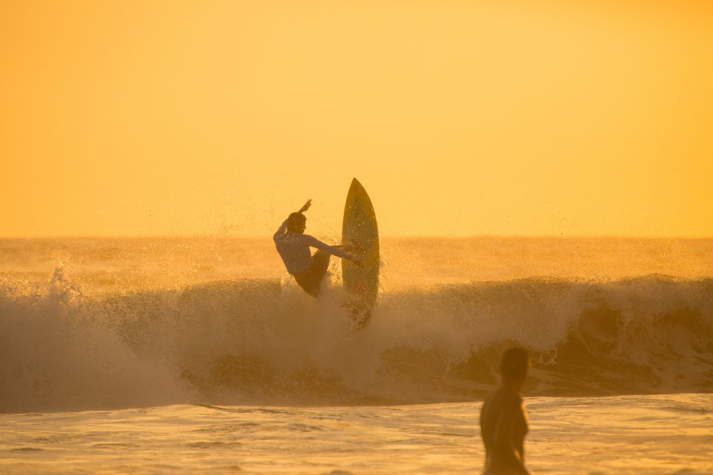 Surfer performing a trick on a wave at sunset